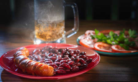 Roasted sausage with beans on a plate.