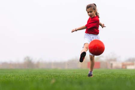 Girl kicks a soccer ball on a soccer field Stok Fotoğraf - 158364006