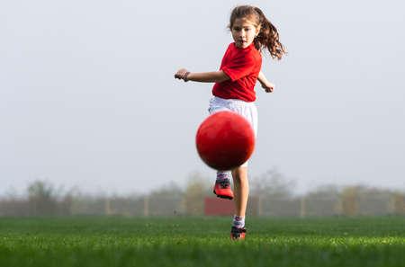 Girl kicks a soccer ball on a soccer field Stok Fotoğraf - 158363760