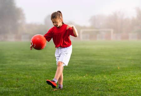 Girl kicks a soccer ball on a soccer field Stok Fotoğraf - 158470426