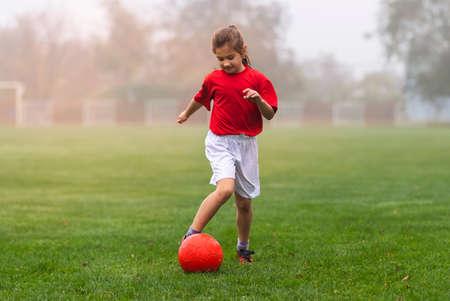 Girl kicks a soccer ball on a soccer field Stok Fotoğraf - 158468520