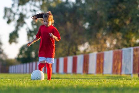 Girl kicks a soccer ball on a soccer field Stok Fotoğraf - 158495952