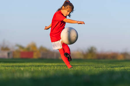 Girl kicks a soccer ball on a soccer field Stok Fotoğraf - 158495850