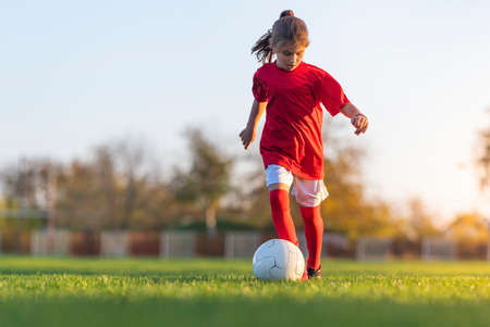 Girl kicks a soccer ball on a soccer field Stok Fotoğraf - 158495962