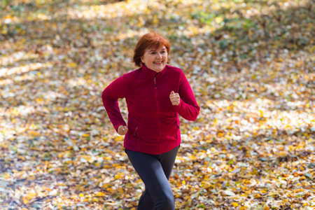 Active middle-aged woman  jogs runs on nature