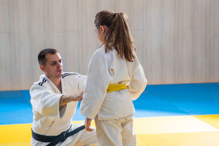 Experienced judo trainer with black belt tying belt for his pupil before competition Stok Fotoğraf