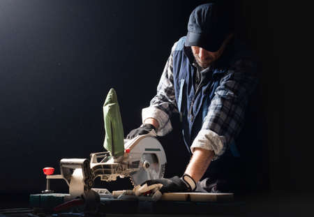 Closeup of young man sawing lumber with sliding compound miter saw indoors. Stok Fotoğraf