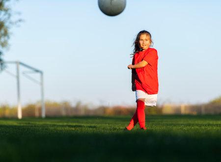 Girl kicks a soccer ball on a soccer field