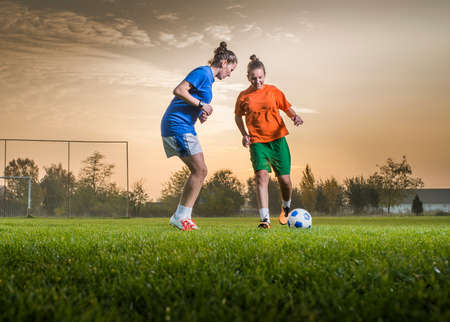 Two female soccer players on the field in sunset