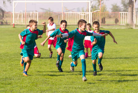 Kids soccer football - happy young children players celebrating in hug after victory
