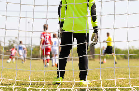 Goalkeeper stands against goal with net and stadium.