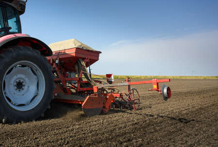 Farmer with tractor seeding crops in the field.