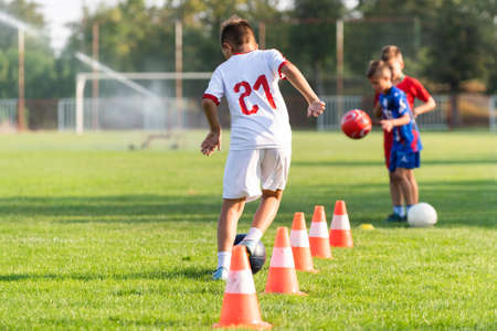 Boys passes soccer ball each other on the football field.