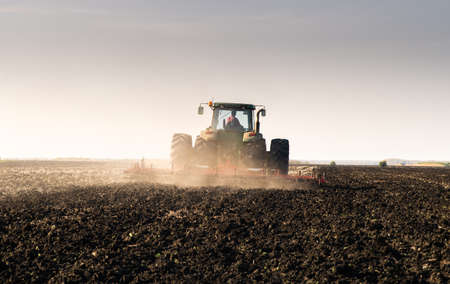 Farmer preparing his field in a tractor ready for spring.