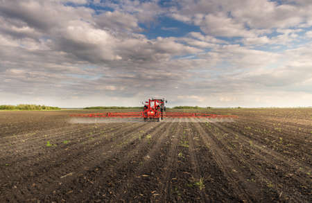 Tractor spraying pesticides on field  with sprayer