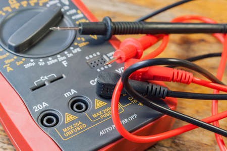 probes: Digital multimeter with the connected probes on a table in a workshop Stock Photo