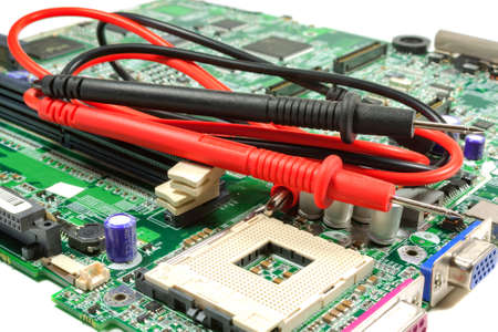 probes: Multimeter probe on the motherboard in a workshop