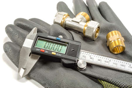 Digital caliper with plumbing fittings and working gloves on a white background Stock Photo