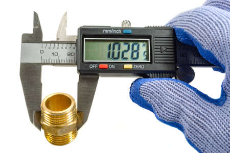 Measurement of plumbing fitting with digital caliper in the masters hand in a glove