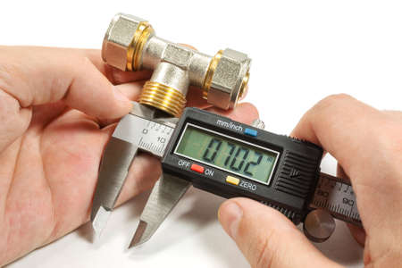 fitting in: Measurement of plumbing fitting with digital caliper in the masters hand Stock Photo