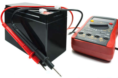 12v: Backup battery with a multimeter and probes on a white background