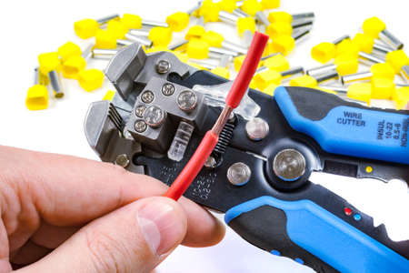 cable cutter: Wires stripper in master hand and cord end terminals on a white background