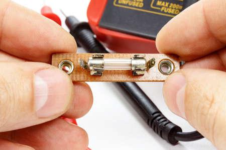 el fusible en las manos de un electricista sobre un fondo blanco