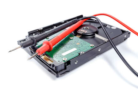 probes: Hard disk drive with multimeter probes on a white background