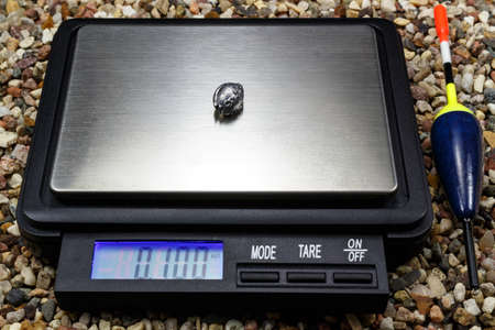 fishing float: Lead weight for fishing float with pocket scale on the stony ground Stock Photo