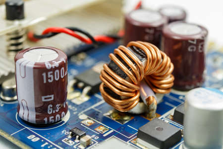 attenuation: Transformer on a ferrite ring on the circuit board closeup Stock Photo