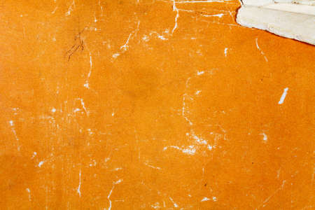 Fragment of a vintage orange paper texture with scrapes and damages. Abstract background