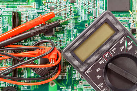 probes: Digital multimeter with probes on a printed circuit board Stock Photo
