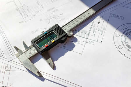 sliding caliper: Digital caliper lies on a engineering drawings