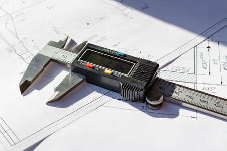 sliding caliper: Electronic caliper lies on a engineering drawings
