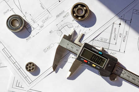 sliding scale: Electronic calipers with ball bearings on a engineering drawings