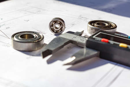 sliding scale: Used ball bearings and electronic calipers on a table closeup