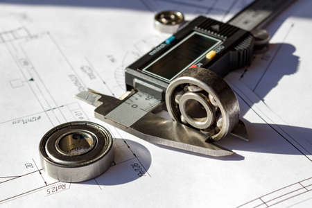 sliding scale: Measuring of the used ball bearings height by electronic caliper Stock Photo