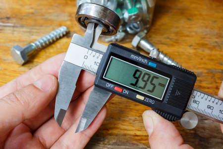 diameter: Measurement the inner diameter of a ball bearing by digital caliper Stock Photo