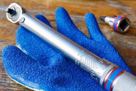 Torque wrench and work glove on the table in workshop Stock Photo