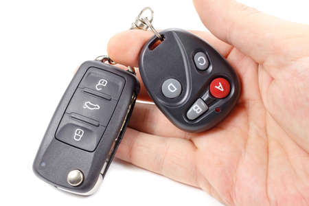 Man holds in hand ignition key and garage door remote control Stock Photo