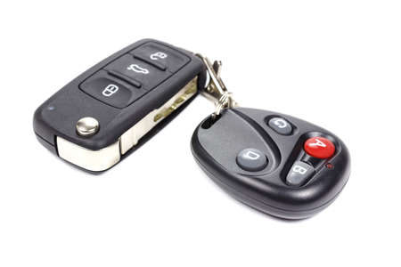 keyless: Garage door remote control with closed ignition key on a white background