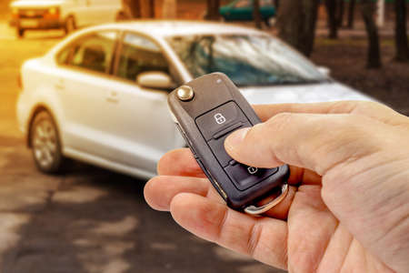 Man presses button on ignition key with immobilizer on the background of the car Standard-Bild