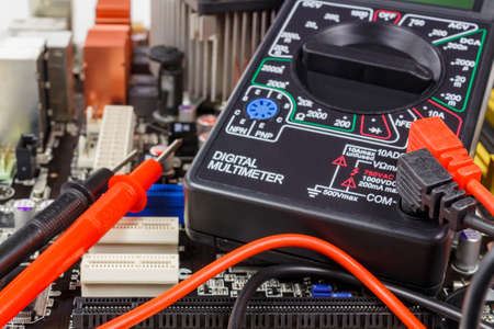 power cables: Digital multimeter with probes on the motherboard surface closeup Stock Photo