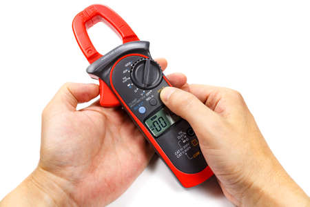 Digital clamp multimeter in mans hand on a white background