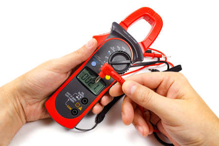 probes: Digital clamp multimeter with probes in mans hand on a white background