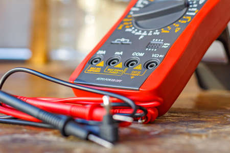 probes: Digital multimeter with probes on a wooden table in the workshop