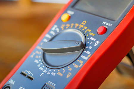 indicate: Digital multimeter on a wooden table in the workshop closeup Stock Photo
