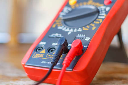 indicate: Digital multimeter with connected probes on a wooden table