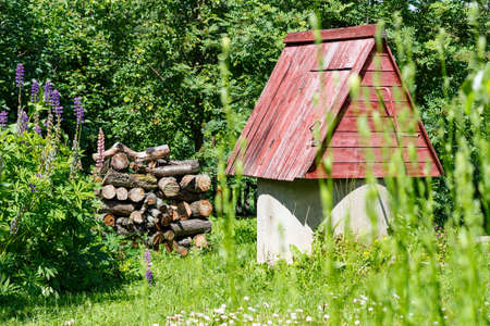groundwater: Rustic wooden water well with woodpile of firewood Stock Photo