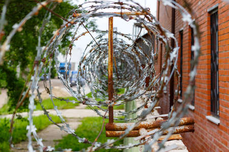 Barbed wire on a concrete fence. Fenced and guarded territory Stock Photo